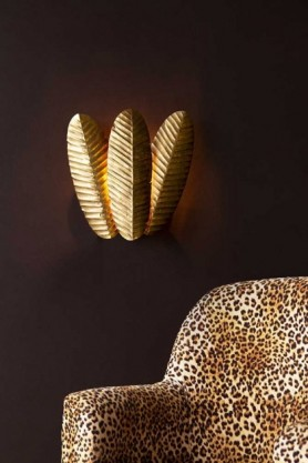 Lifestyle image of the Banana Leaf Trio Wall Light switched on with Rockett St George Leopard Love Armchair and dark wall background