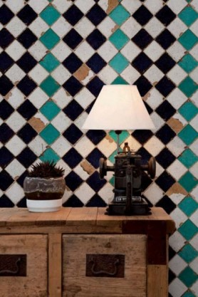 Lifestyle image of Turquoise Chess Wallpaper with wooden cabinet and white shade table lamp