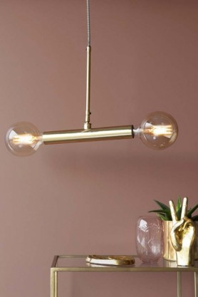 Lifestyle image of twin bulb ceiling light turned on over gold side table with plant on it and mauve wall background