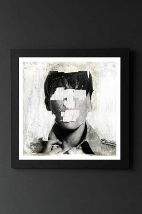 lifestyle image of Unframed Faceless No. 2 Fine Art Print black and white portrait of boy with eyes and mouth whited out in black frame on dark wall background