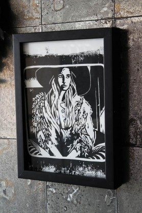 lifestyle image of Unframed Limited Edition Hippie Art Print By Anna Hayman in black box frame on distressed grey tiled wall