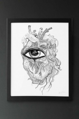 lifestyle image of Unframed Limited Edition Sea Heart Art Print black and white eye inside anatomical heart in black frame on grey wall background