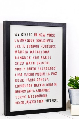 lifestyle image of Unframed Personalised Kiss Typographic Art Print in black frame on white table with small plant