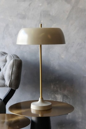 lifestyle image of Ventura Table Lamp - Bone on gold side table and grey cloud chair with distressed grey wall background