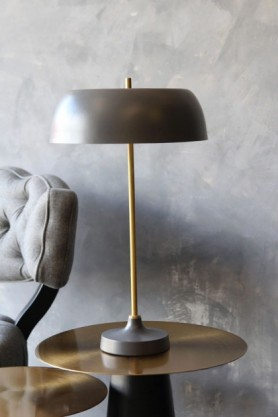 lifestyle image of Ventura Table Lamp - Dark Grey on gold side table with grey cloud chair and distressed grey wall background
