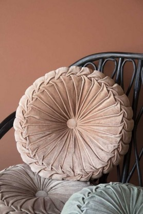 Lifestyle image of the Vintage Style Velvet Rouched Round Cushion in Soft Pink on black rattan chair with emanuella painted wall background