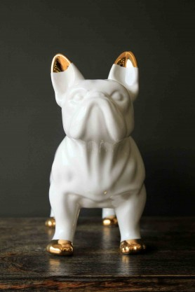 lifestyle image of front of White ceramic bulldog with golden ear tips and paws on dark wooden surface and dark wall background