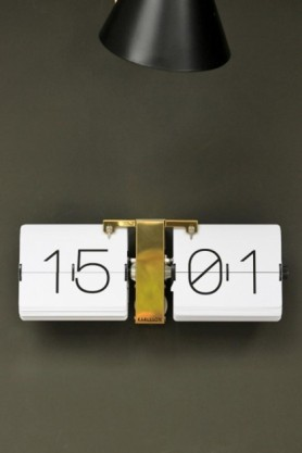 lifestyle image of White flip clock with brass stand featured under a black lampshade with black ceiling light and dark grey wall background