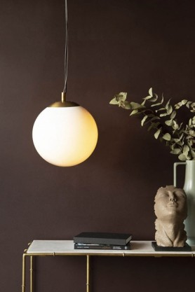 Lifestyle image of the Atlas Globe Pendant Light switched on above marble and gold console table with Distressed Stone Effect Resting Head Ornament and eucalyptus with dark wall background