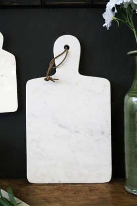 Lifestyle image of the White Marble Paddle Chopping Board on wooden shelf with green vase in corner and dark wall background