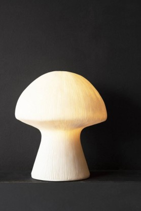 lifestyle Image of the White Sandstone Mushroom Table Lamp lit up on dark wall background