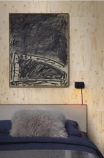 lifestyle image of NLXL PHM-37 Plywood Wallpaper By Piet Hein Eek in bedroom with bed with dark bedding and grey art work on wall