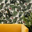 square lifestyle image of Witch & Watchman Amazonia Wallpaper - Light with yellow sofa and plant