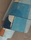 detail image of roll of lifestyle image of Smink Things Quarter Circle Blue Tile Wallpaper with blue and wood chair