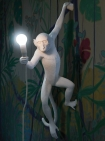 Left-Hand Hanging Monkey Wall Lamp - White on floral wall background with light on lifestyle image