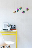 Lifestyle shot of the white tile wallpaper with a yellow desk and geometric pendant lights - Rockett St George