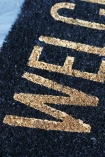detail image of writing on Black & Gold Welcome Doormat