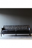 Square lifestyle image of Black Leather Chesterfield 3 Seater Sofa on grey rug and dark wall background
