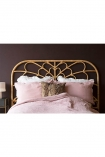 Full width landscape lifestyle image of the Bloom Natural Rattan Headboard - Double Bed with pink bedding and dark wall background