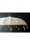 landscape lifestyle image of Boho Beaded Cotton Garden Umbrella on dark wall background