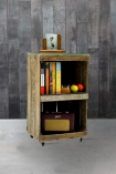 lifestyle image of Crate Side Table By Ines Cole with books and other ornaments inside on grey flooring and distressed grey wall background