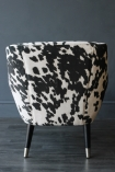 detail image of back of Faux Cowhide Vintage Style Armchair on wooden floor and dark grey wall background