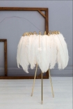 Feather Table Lamps In Black Or White on pale background and wooden detail in background lifestyle image