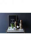 lifestyle image of Makrana Marble Drinks Trolley with black message board and gold drink accessories and dark grey wall background