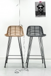 Lifestyle image of Blonde Rattan Bar Stool and Black Rattan Bar Stool next to each other on white flooring and white wall background