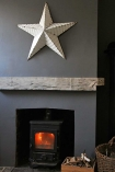 lifestyle image of Vintage Metal Star - White above fireplace and grey wooden panel and dark grey wall background