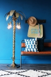 Palm Tree Floor Light with blue background beach supplies monochrome rug and brown bench lifestyle image