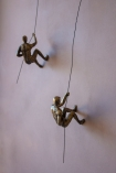 Image of both the left & right handed Abseiling Man In Antique Gold climbing the wall