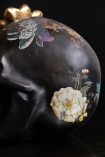 Close-up image of the detail on the Black Feminine Skull With Gold Flower Ornament