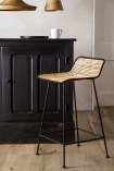 Close-up lifestyle image of the Black Framed Natural Rattan Bar Stool
