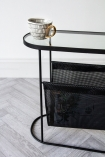 Image of the end of the Black Lozenge Shaped Glass Side Table With Magazine Rack