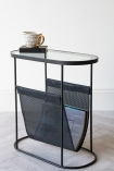 angled image of the Black Lozenge Shaped Glass Side Table With Magazine Rack