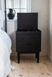 Lifestyle image of the Bureau-Style Black Mango Wood Bedside Table with the lid open