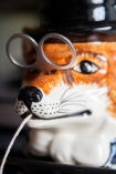 Close-up of the face on the Hand Painted UK Made Fox String & Scissor Holder with scissors for glasses & string coming out his mouth