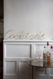 Front on lifestyle image of the Cocktails Typography Gold Metal Wall Art