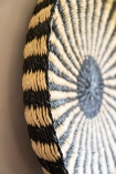 Close-up of the side of the Ethnic Black & Natural Woven Display Tray