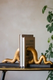 Close-up lifestyle image of the Gold Snake Bookends with books