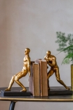 Close-up lifestyle image of the Antique Gold Strong Man Bookends