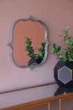 Angled lifestyle image of the Indoor Or Outdoor Marrakesh Mirror hanging on a wall
