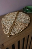 Lifestyle image of the Leaf Shaped Seagrass Placemat In Natural on a sideboard