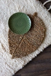 Lifestyle image of the Leaf Shaped Seagrass Placemat In Natural with a plate