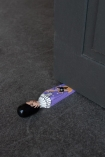 Lifestyle image of the Purple Prince Doorstop wedged under a door