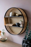 Side angle lifestyle Image of the Round Woven Cane Rattan Shelf Unit