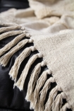 Close-up image of the tassels on the Ivory Cream Soft Cotton Tufted Stripes & Dot Throw