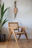 Right angled lifestyle image of the Woven Cane Mango Wood Armchair