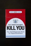 detail image of box on 50 Things That Might Kill You The Self-Diagnosis Card Deck For Hypochondriacs on black table